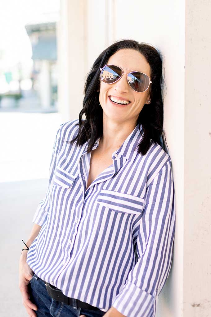 Laura leaning against wall with sunglasses on