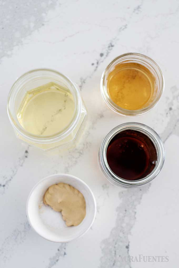 ingredients for maple dijon dressing set out in cups on countertop