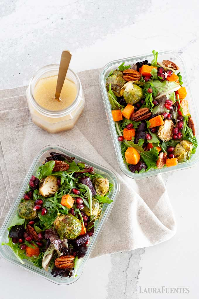 two salads in glass containers with maple dijon dressing in a jar to one side