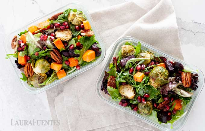 two meal prep containers with winter salad