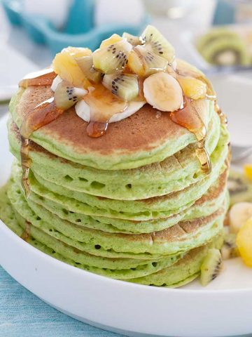 large stack of green spinach pancakes topped with fruit