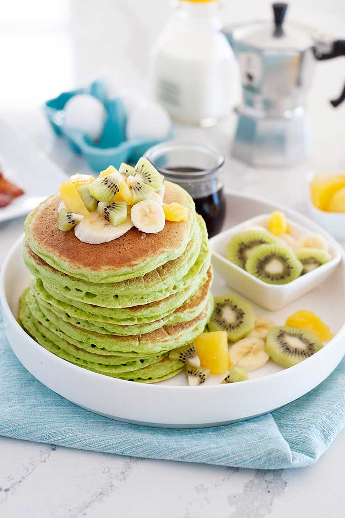 large stack of green pancakes with kiwi slices