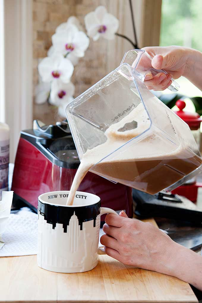 bulletproof coffee being poured from blender into mug