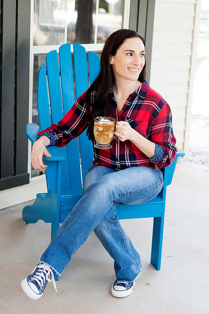 Laura sitting in blue chair with cup of cold coffee