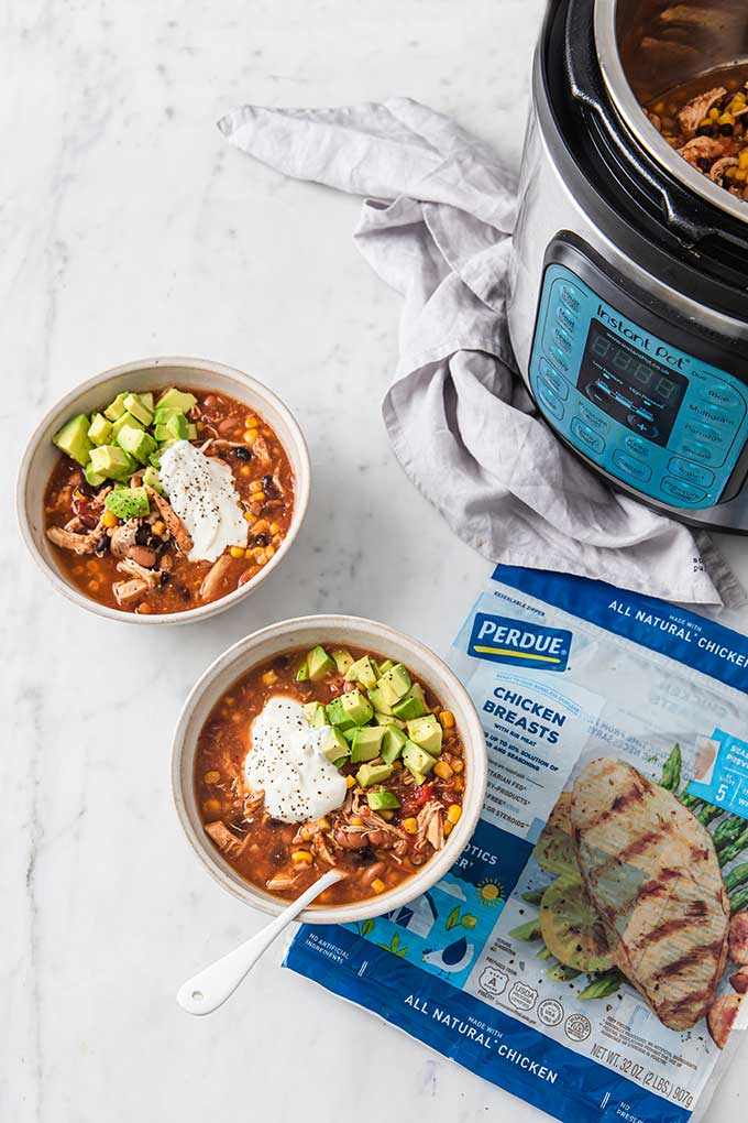 two bowls of chicken taco soup next to instant pot with bag of perdue chicken to one side