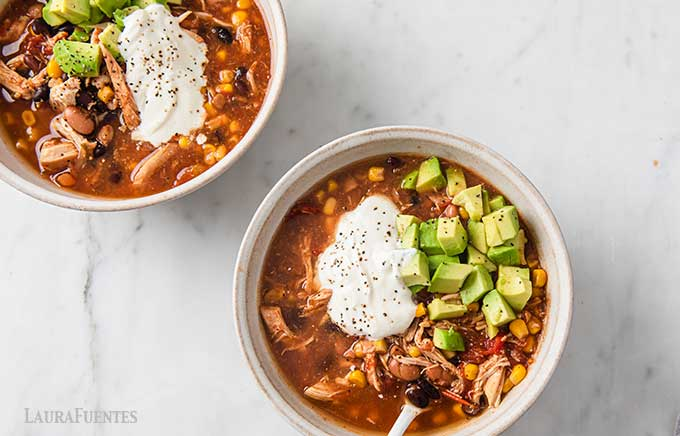 two bowls of chicken taco soup topped with avocado and sour cream