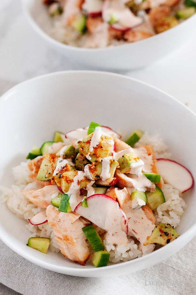 two salmon and rice bowls with spicy dressing
