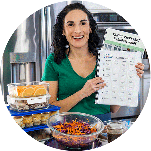 Laura standing behind containers ofmeal prep with recipe documents