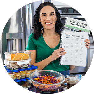 laura holding meal plan guide in front of prepped food