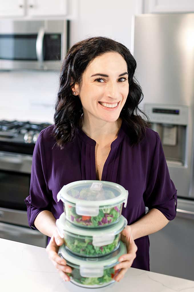 Laura holding salads in meal prep container