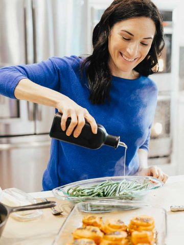 Woman pouring oil over vegetables