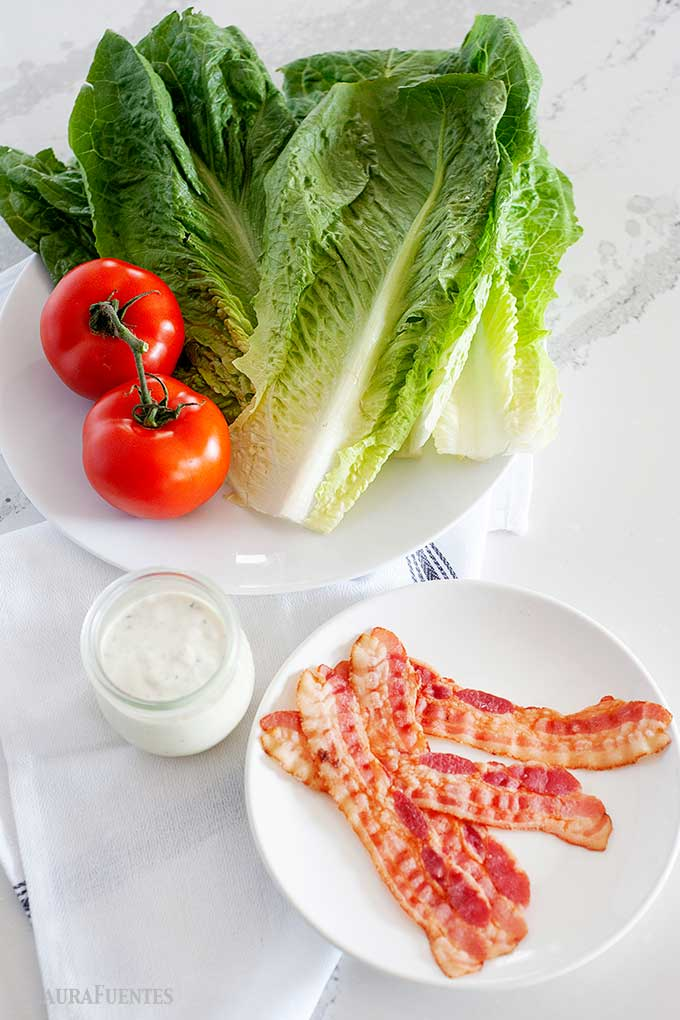 bacon strips, dish of homemade ranch, two tomatoes and large pieces of lettuce on a plate
