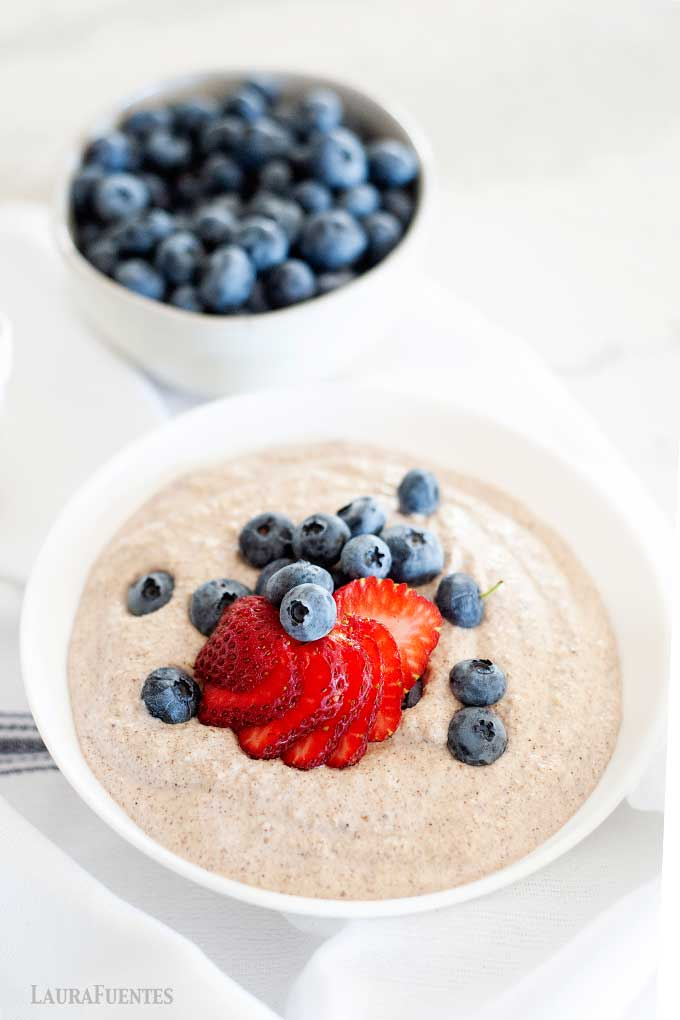 bowl of grain free oatmeal with berries on top. small bowl of blueberries to one side