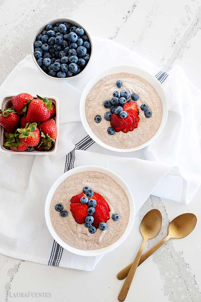 overhead view of two bowls of oatmeal and berries