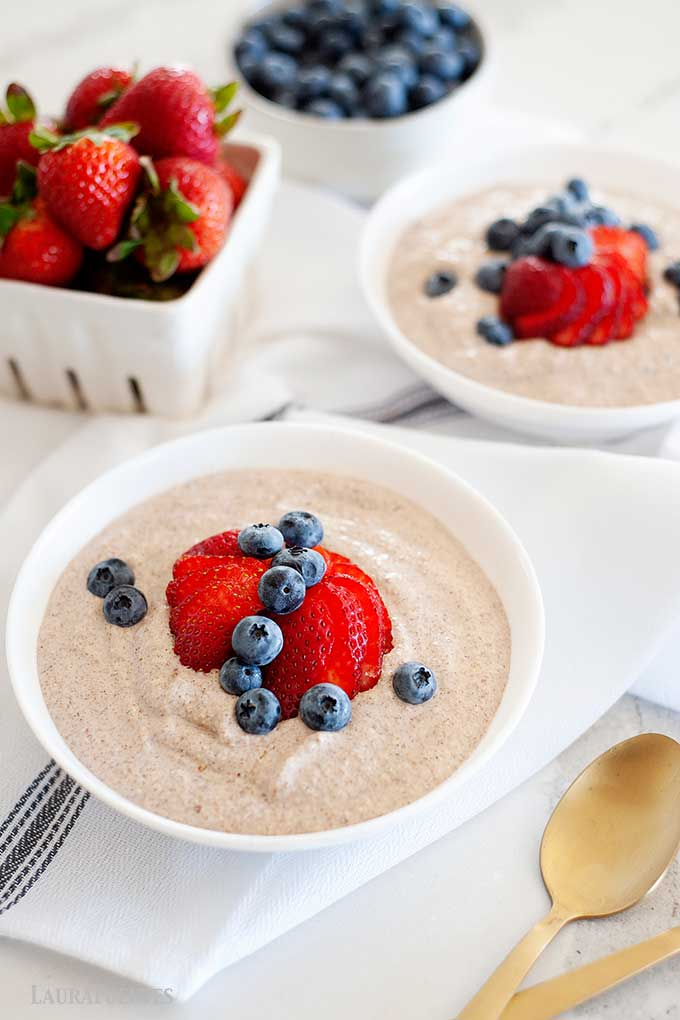 two bowls of grain free oatmeal topped with blueberries and strawberries