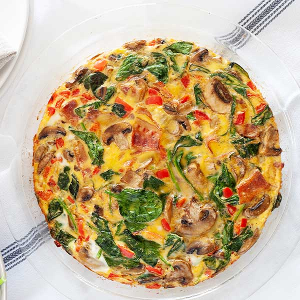 spinach bacon frittata in a round glass dish