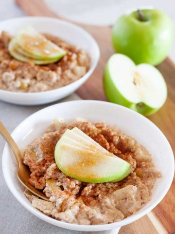 two large bowls of oatmeal topped with apple slices and brown sugar