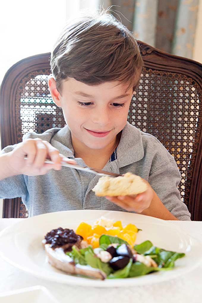 boy buttering biscuit at table