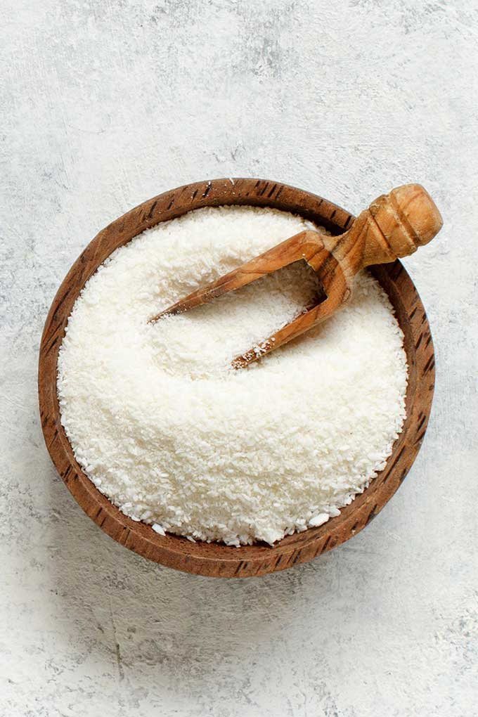 wooden bowl of coconut flour with measuring spoon