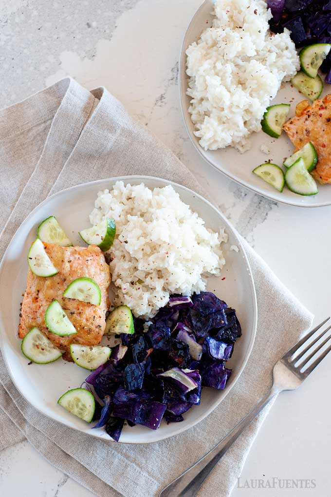 two plates topped with rice, purple cabbage and maple miso salmon