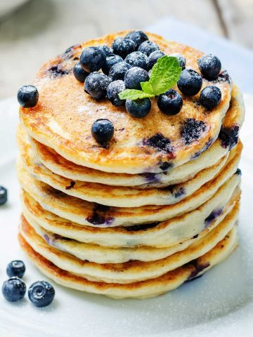 large stack of blueberry pancakes topped with blueberries