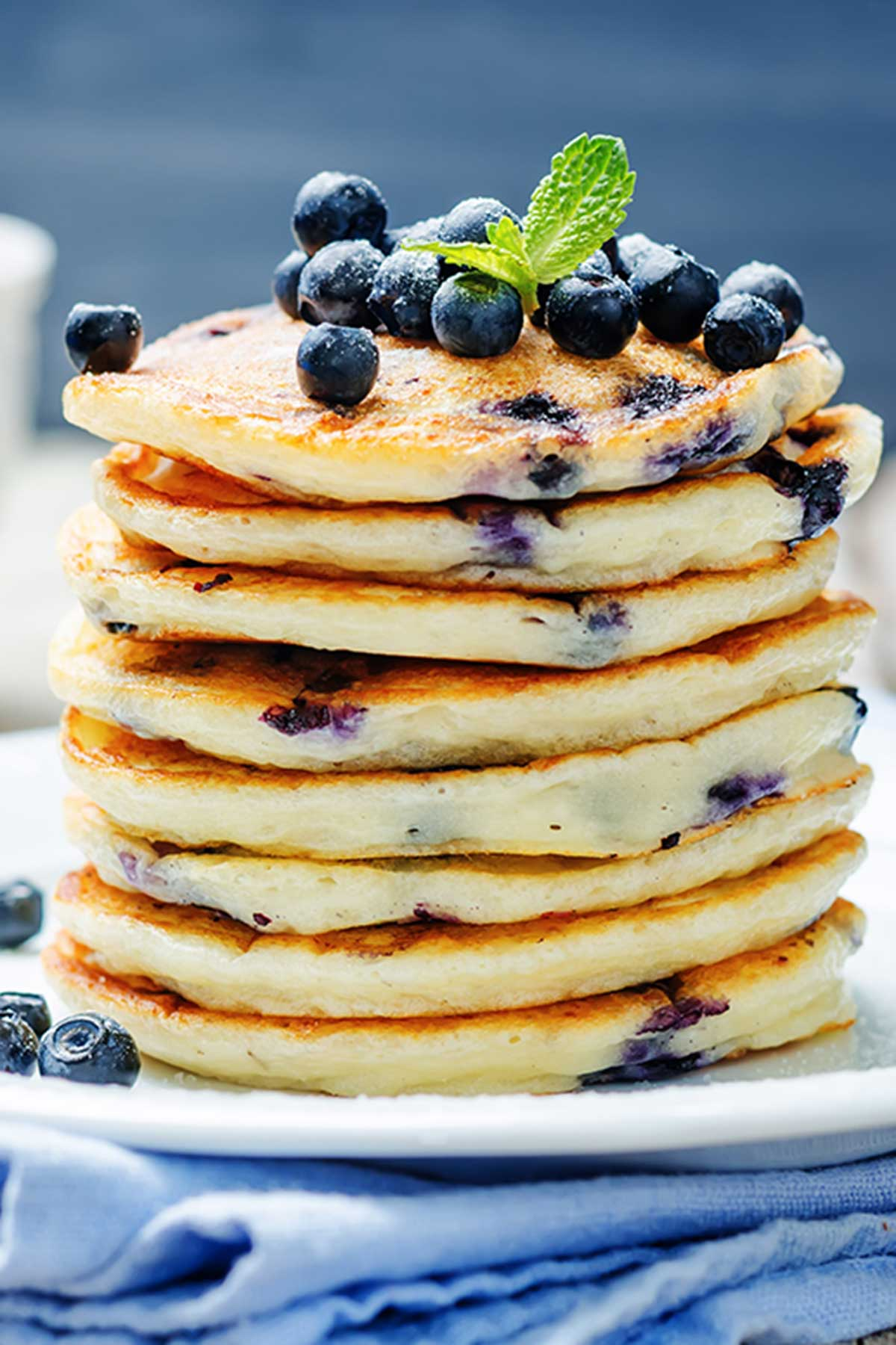 large stack of blueberry pancakes viewed from the side