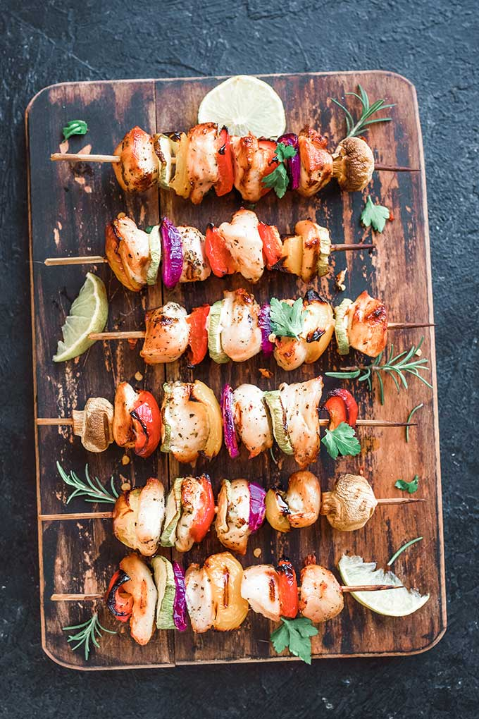 row of chicken and vegetable kabobs on a cutting board