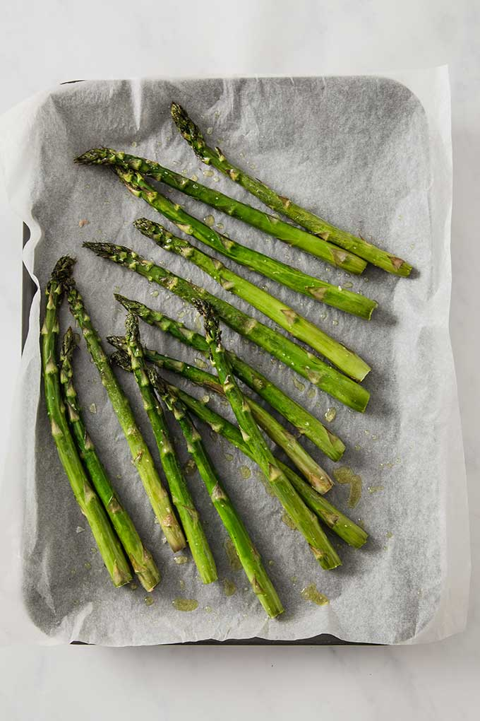 roasted asparagus on a baking sheet covered with parchment paper