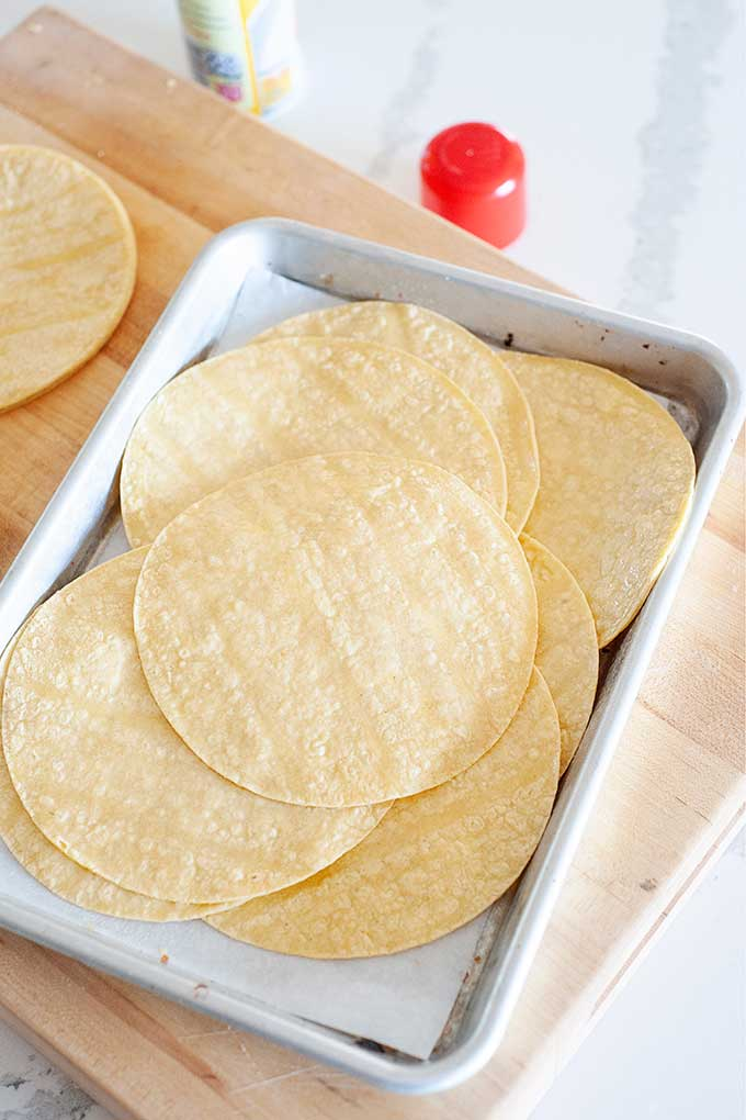 tortillas on a baking sheet getting ready to be warmed