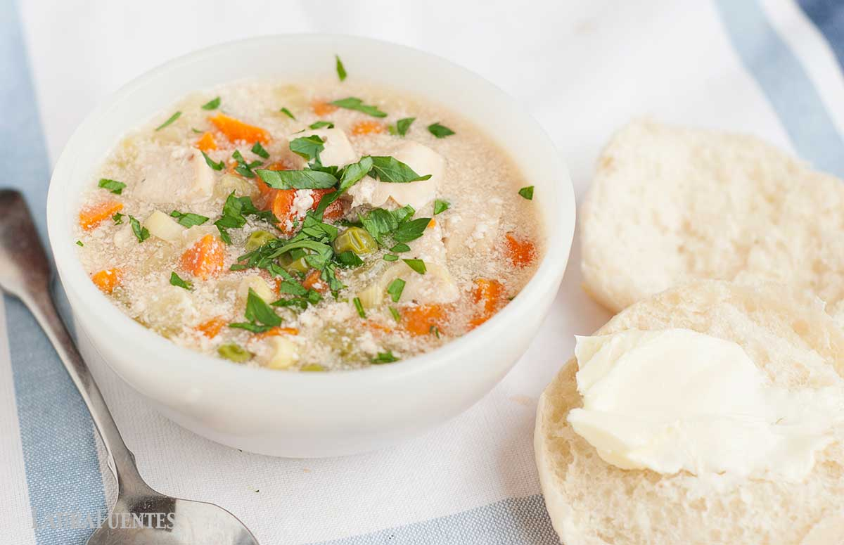 a bowl of chicken pot pie soup with biscuits to one side
