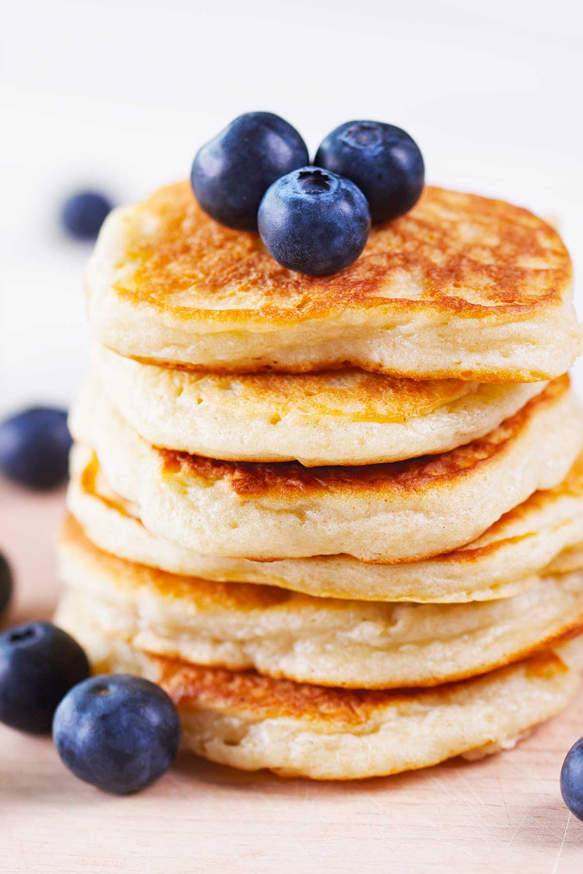 large stack of coconut flour pancakes topped with blueberries