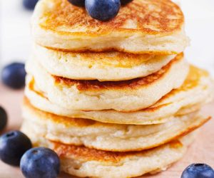 coconut flour pancakes in a stack with blueberries