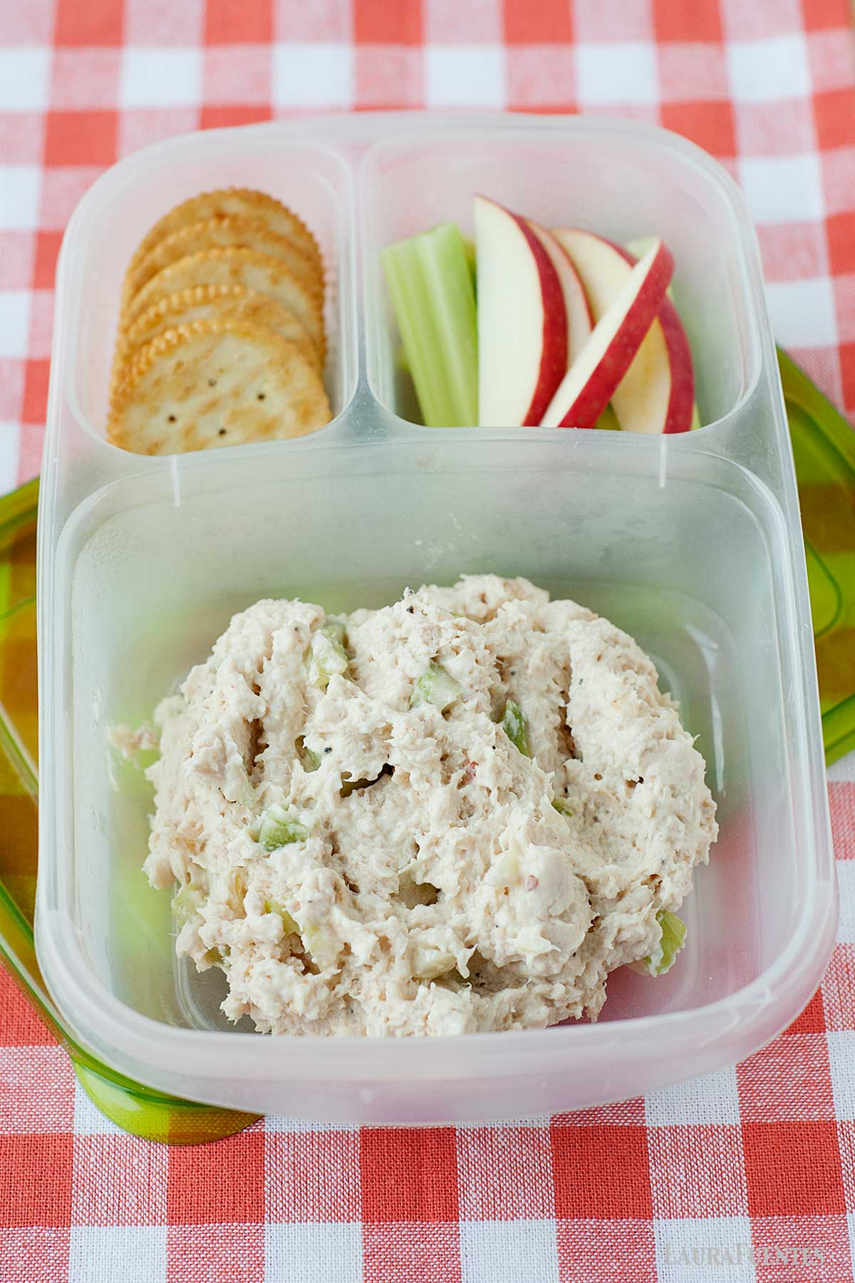 healthy southern chicken salad in a lunchbox with crackers, celery, and sliced apples.