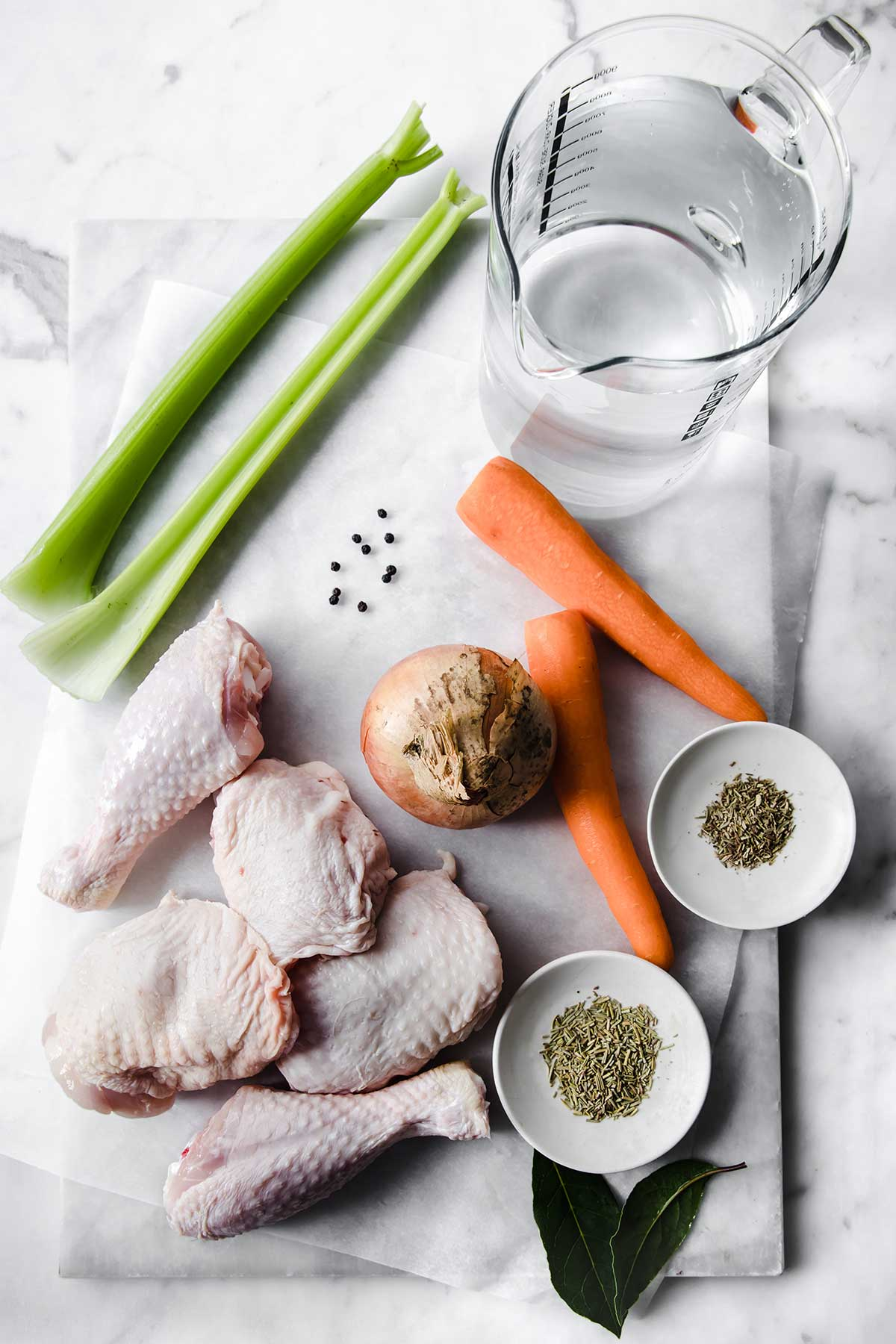 Flat lay photo of ingredients for homemade chicken broth. Chicken thighs and legs, carrot sticks, celery sticks, bay leaves, an onion and spices.