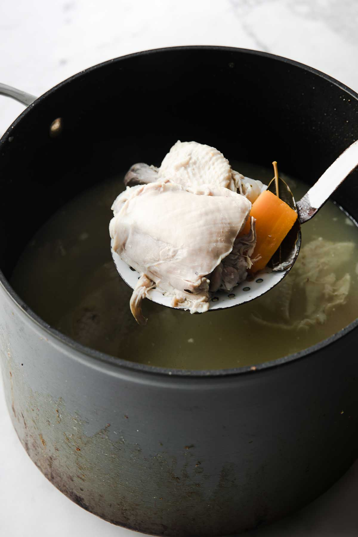 Using a slotted spoon to pull out chicken thighs from stock pot.