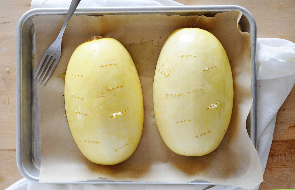 two spaghetti squash halves on a baking sheet holes have been poked in the skin of the squash with a fork.