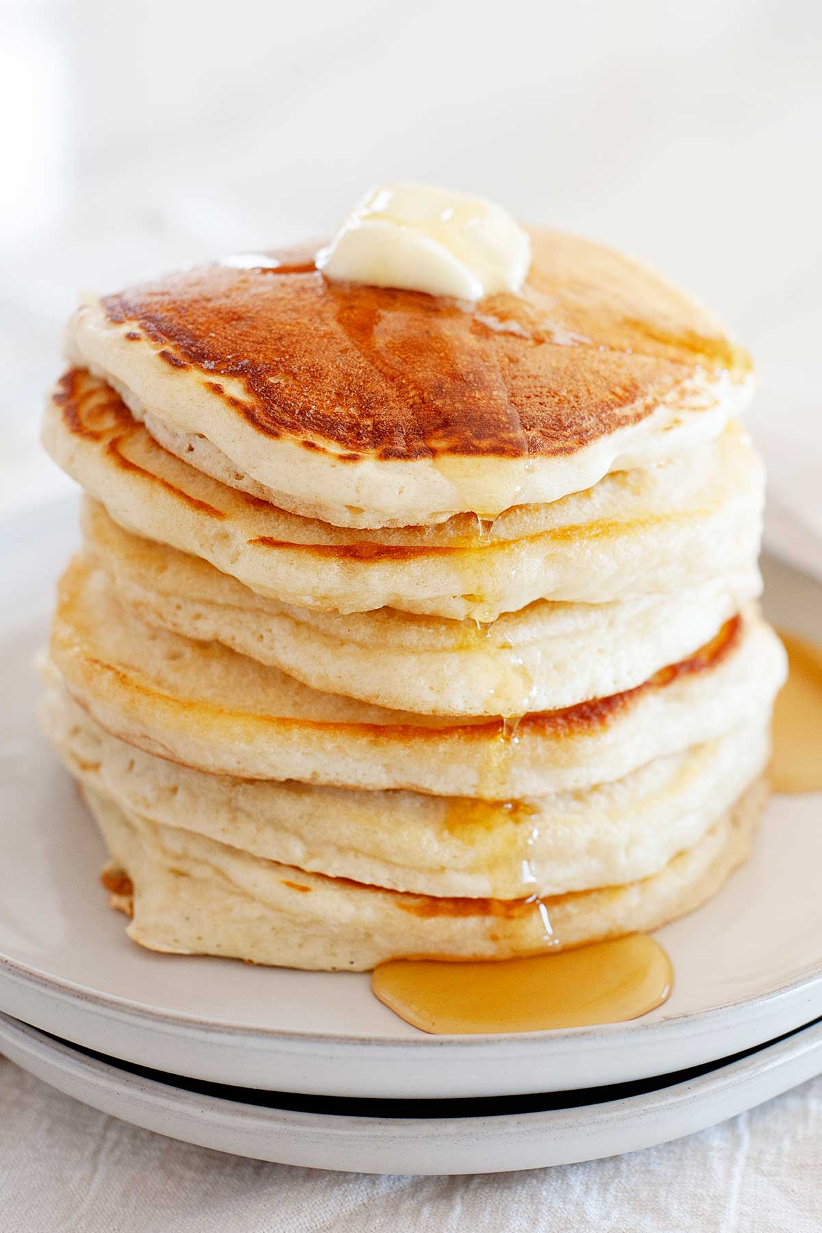 Image: Stack of pancakes topped with butter and syrup.
