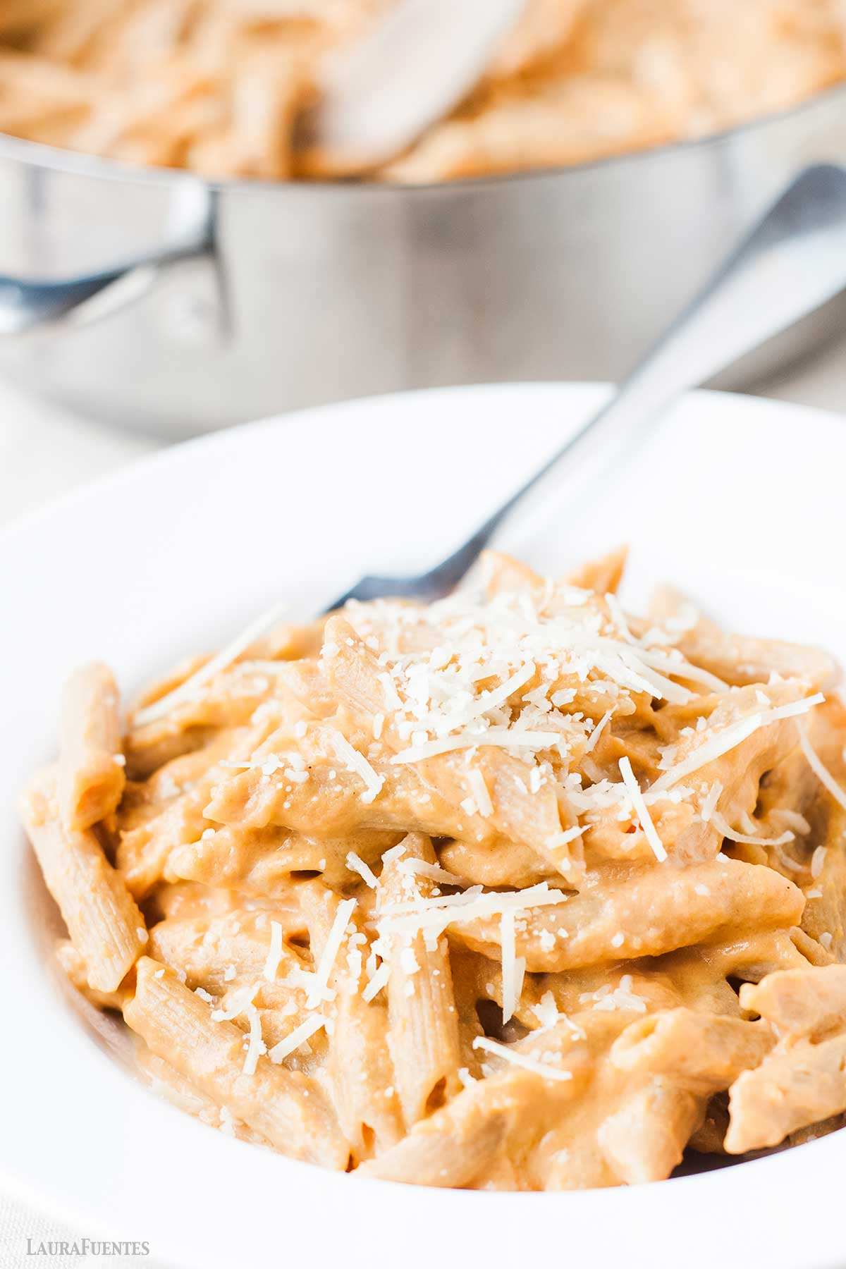 homemade pumpkin pasta in a white plate topped with cheese.