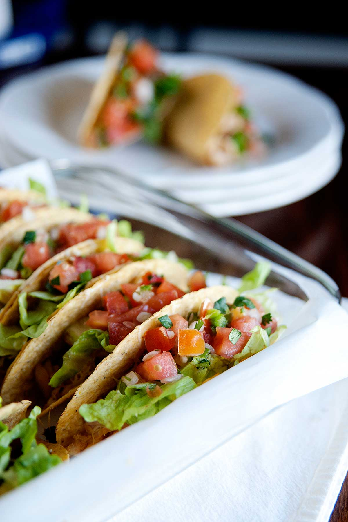 closeup of hard shell tacos in a baking dish. Two tacos on a plate in the background.