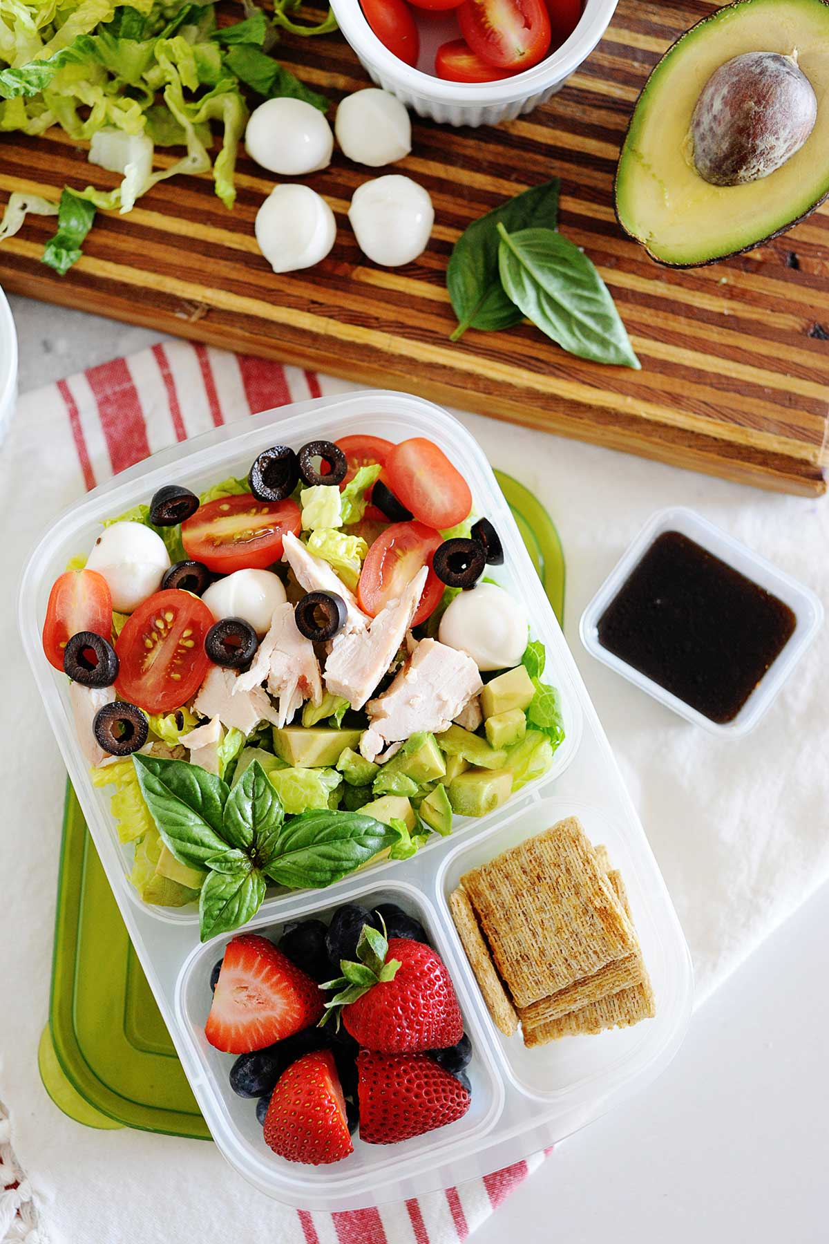 chicken caprese sald in a lunch container with berries and crackers