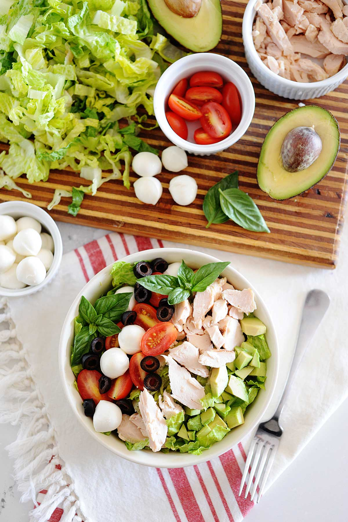 bowl of chicken caprese salad with ingredients on a cutting board.