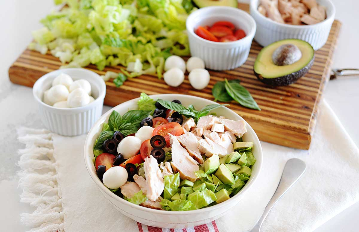 Large bowl of chicken salad with tomatoes, olive slices, halved cherry tomatoes, mozzarella balls and diced avocado.
