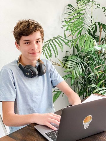 teen boy sitting at table doing homework on a laptop
