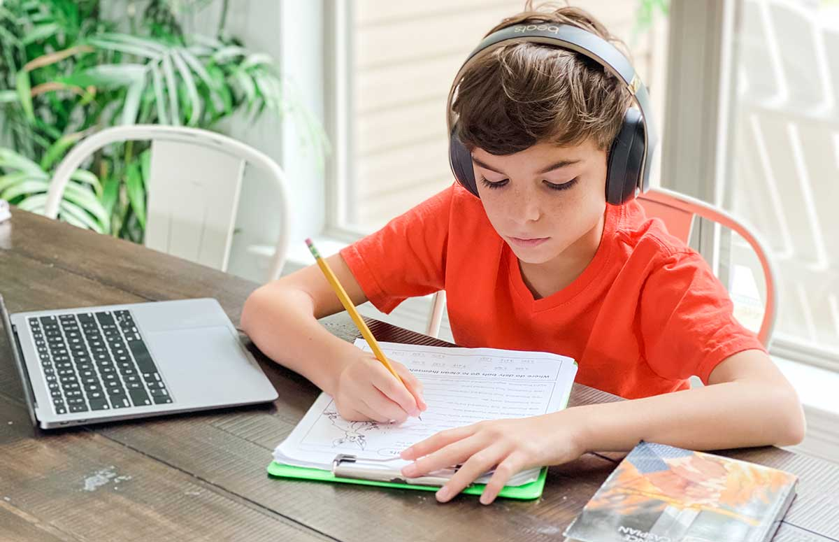 young boy at table doing schoolwork