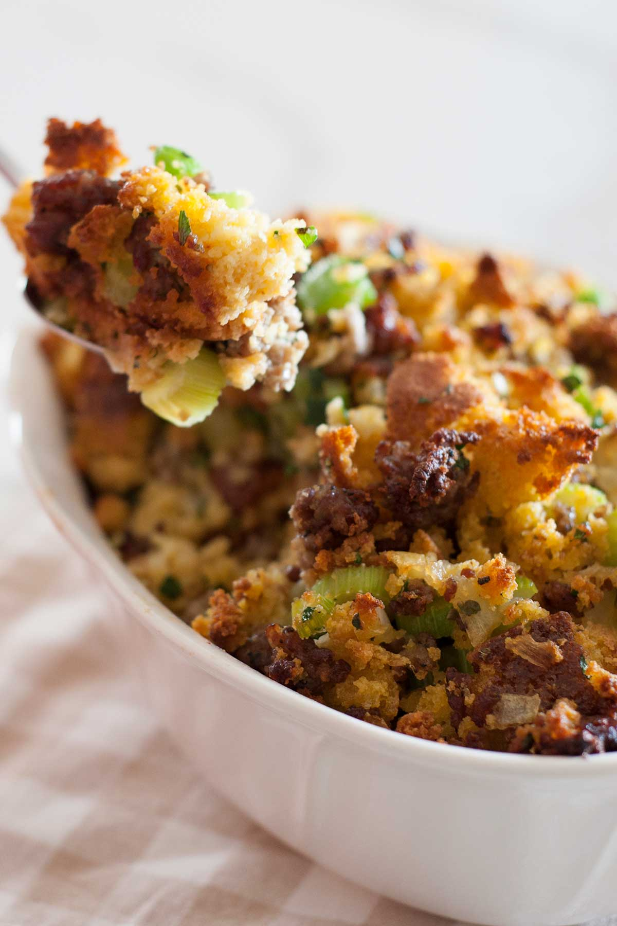 dish of cornbread stuffing with spoon pulling out of it