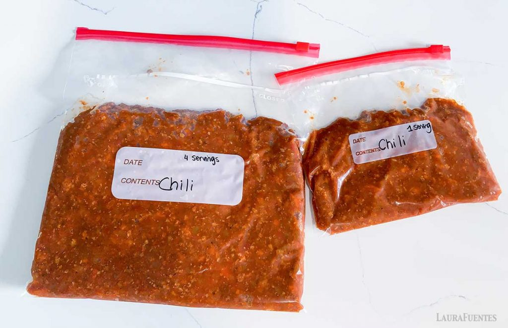 two bags of frozen chili side by side on a countertop