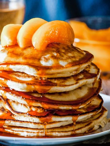 large stack of pancakes topped with peach slices