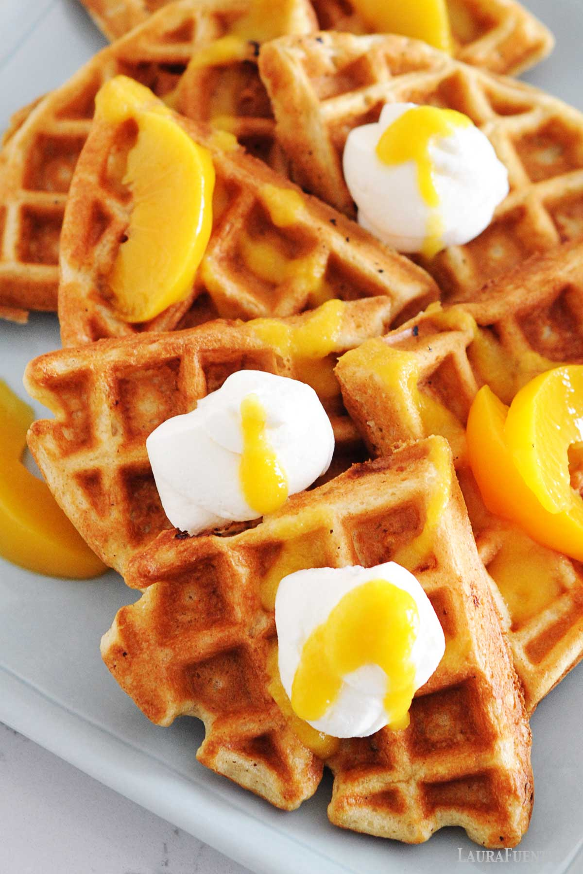 waffles topped with peac slices and peach syrup