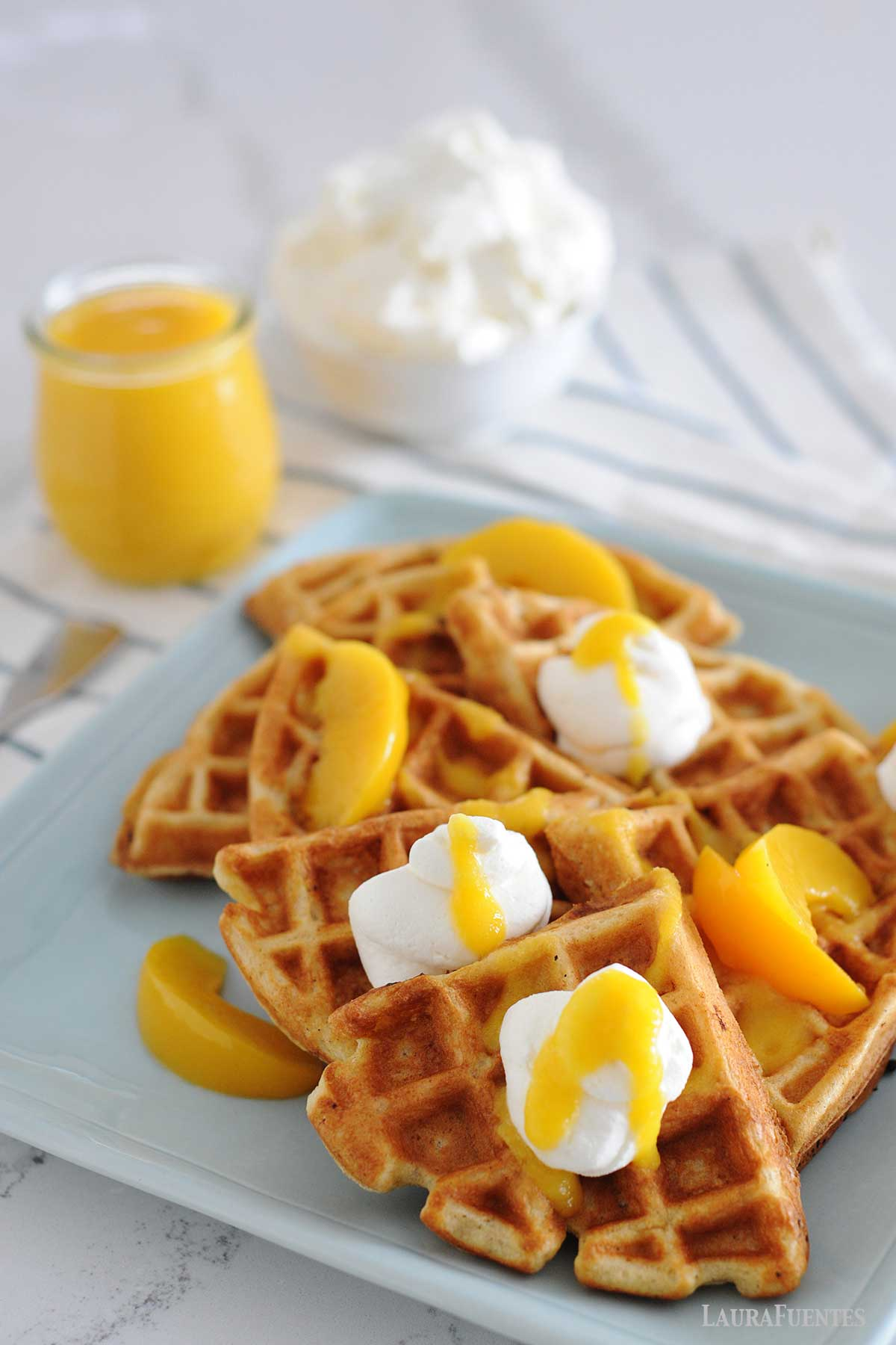 peach waffles with small bottle of peach syrup to one side