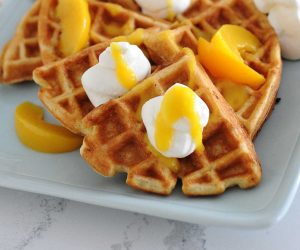 waffles topped with whipped cream and peach syrup